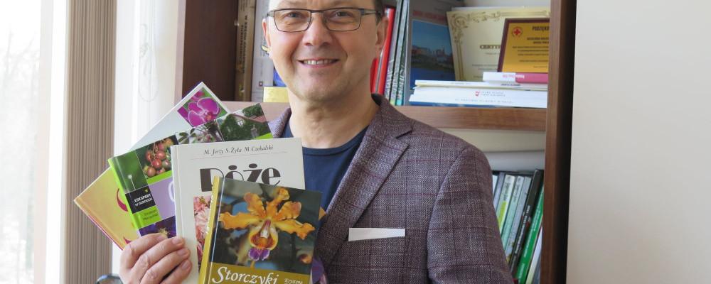 Dyrektor KBP, Dariusz Pawlikowski trzyma w rękach książki o kwiatach