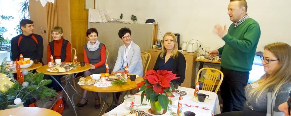 """Spotkanie świąteczne czytelników """"książek mówionych"""". Dyrektor Koszalińskiej Biblioteki Publicznej wita gości zgromadzonych podczas spotkania. Zgromadzeni siędzą przy zastawionych stołach."""