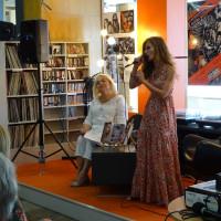 Od lewej: Alicja Flis, Jola Tubielewicz podczas występu. Alicja Flis siedzi, Jola Tubielewicz śpiewa na stojąco.