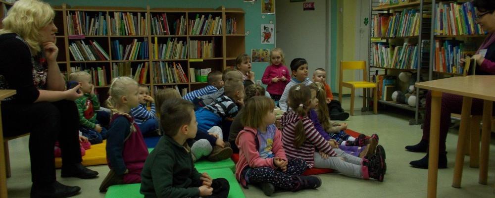 Przedszkolaki siedzące na kolorowych materacach w wypożyczalni dziecięcej filii nr 9. Pani czyta opowiadanie.