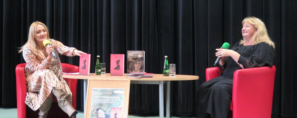 Od lewej: Prowadząca spotkanie Alicja Balcerzak, Adela Kuik-Kalinowska. Obie siedzą na czerwonych fotelach przy stoliku.