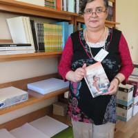 Pracownica Oddziału Magazynów Małgorztaa Jasińska stoi na tle regału  z polecaną przez siebie książką