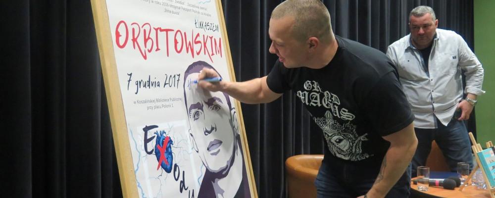 Łukasz Orbitowski składa pamiątkowy autograf na plakacie promującym spotkanie
