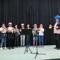 """Występ zespołu """"Mali trębacze"""" z Państwowego Zespołu Szkół Muzycznych wraz z muzykiem Edwardem Klepczyńskim. Siedmiu muzyków (dwie dziewczynki i pięciu chłopców) ma na sobie kolorowe kapelusze. Dyrygent stoi z boku, z prawej strony, ma na sobie błękitną perukę."""