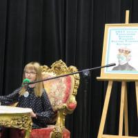 Uczestniczka konkursu Mistrzowie Pięknego Czytania 2018 czyta siedząc na stylowym krześle przy stylowym stoliku.