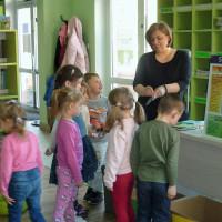 Bibliotekarka pokazuje dzieciom portfel wykonany z kartonu na mleko