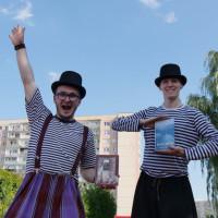 Dwaj panowie chodzący na szczudłach pomagają koszalińskim bibliotekarzom promować modę na czytanie. Oboje trzymają w rękach książki.